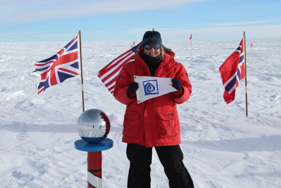 Jamie Hensel (S'03) stands holding the Williams-Mystic burgee at the ceremonial South Pole.