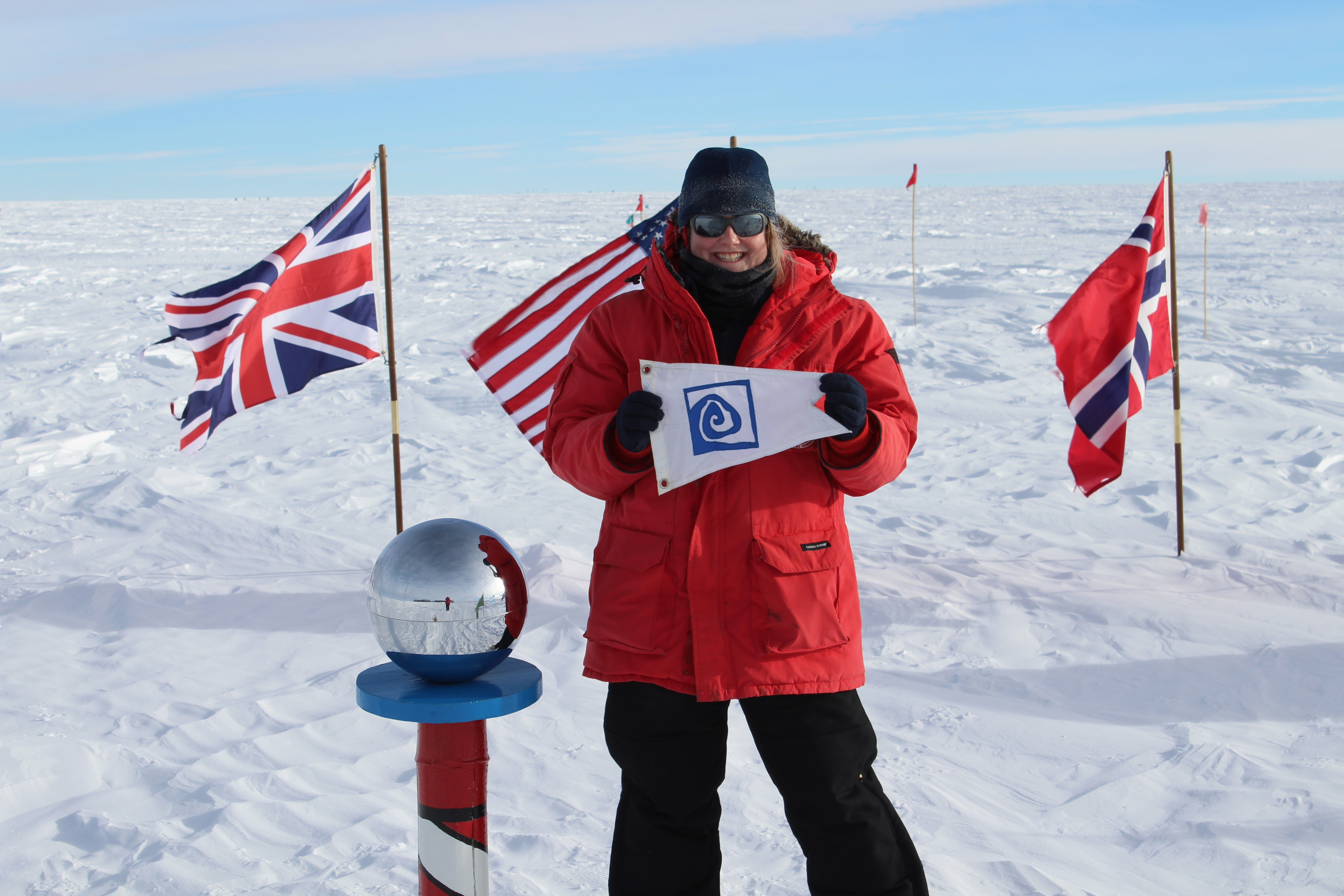 Spring 2003 alumna Jaime Hensel stands at the ceremonial South Pole with the Williams-Mystic burgee in hand.