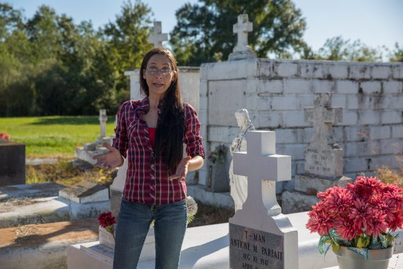 A woman speaks in front of a cemetery