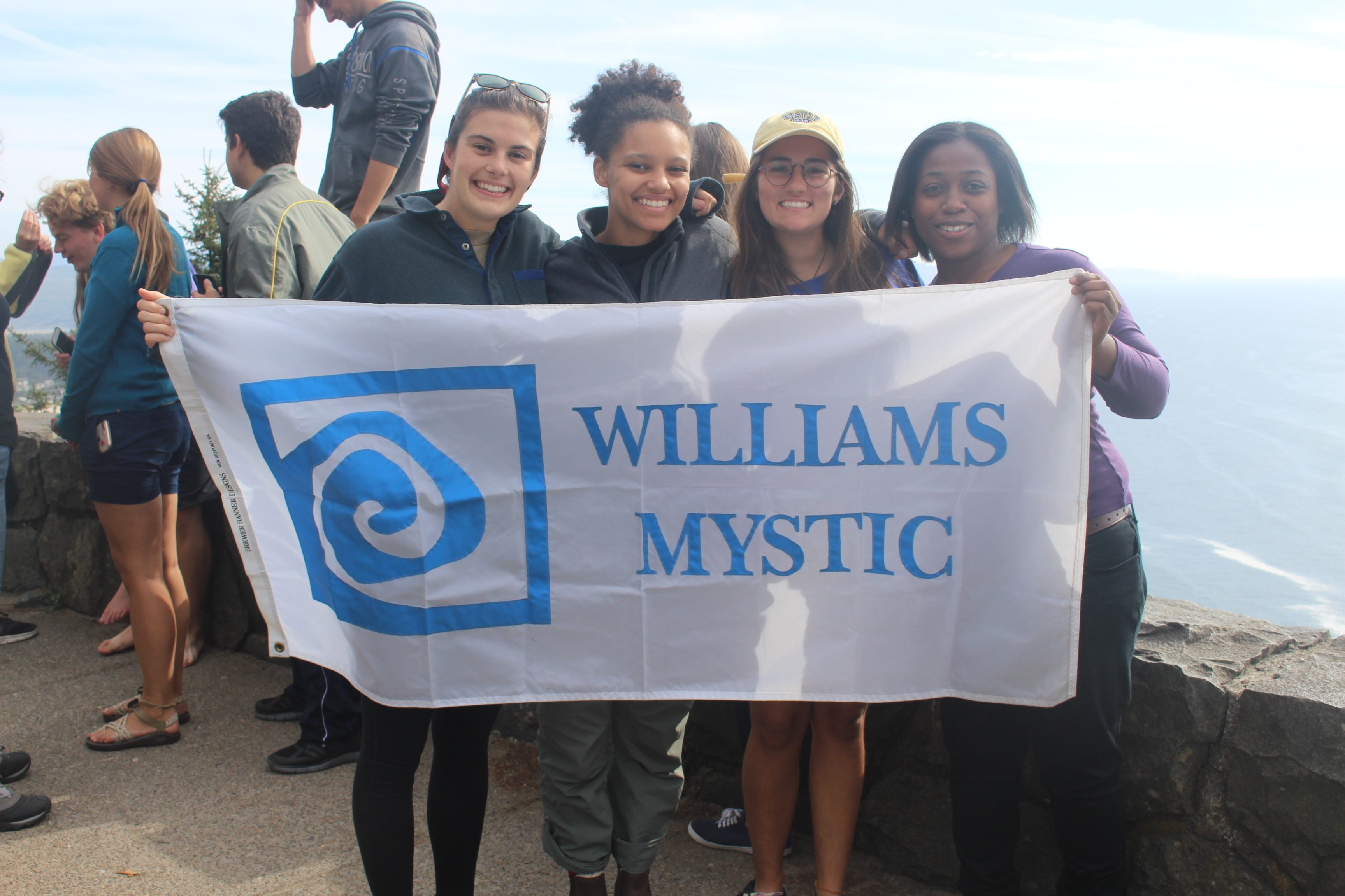 four students grin, holding a Williams-Mystic banner