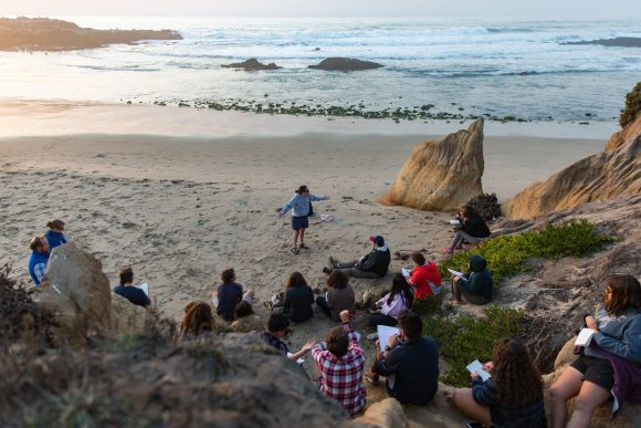 Picture shows students sitting on the rocky edge of a broad beach while a professor lectures standing on the sand below