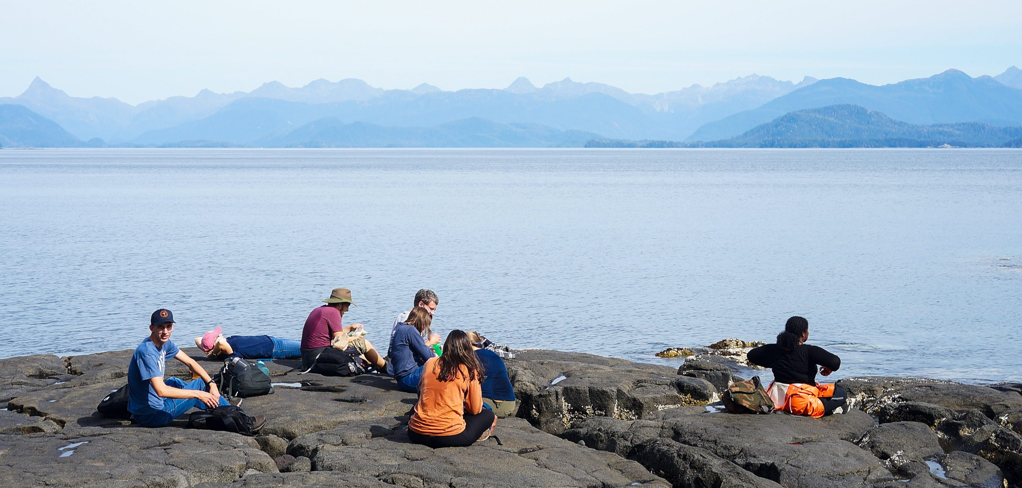 Image shows students sitting on a stark, rocky shore, overlooking a bay with mountains shrouded in fog on the opposite shore