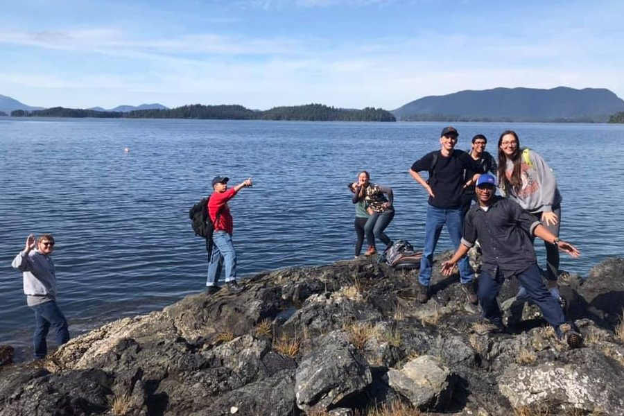 Picture shows students posing and waving on a rocky outcropping into an Alaska inlet, with mountains in the background