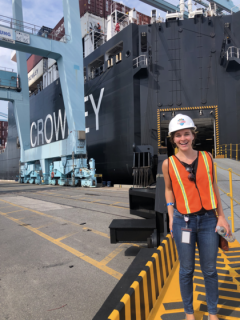 picture shows a woman in a hard hat and safety vest smiling in front of a large container ship