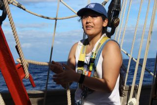 Image shows Dayana aboard a ship in a safety harness