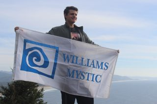 Image shows Devon holding a Williams-Mystic banner in front of a sweeping ocean view