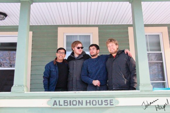 Image shows four young men on the porch of Albion house