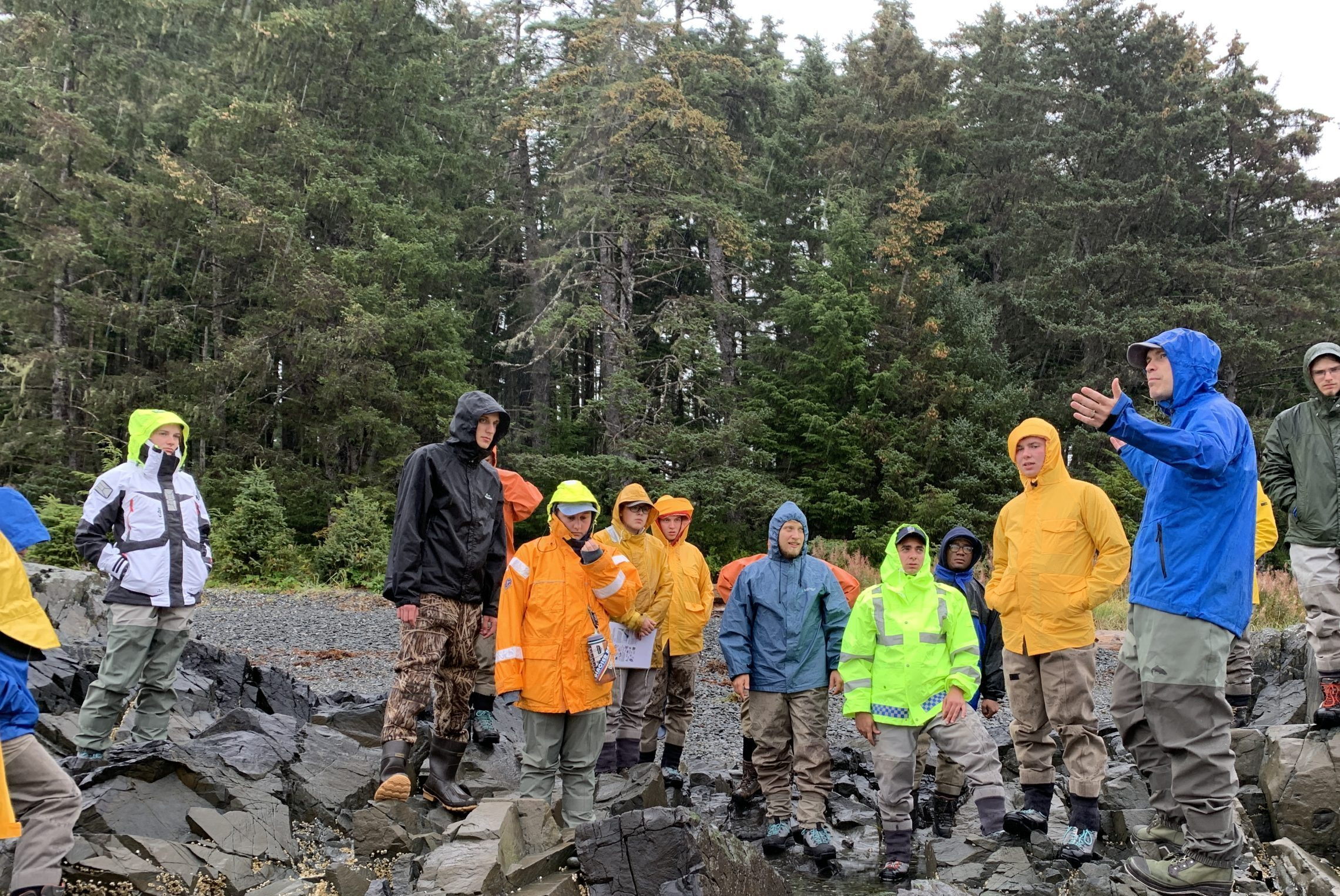 image shows students standing around ecology professor Tim Pusak learning about tide pools in Alaska